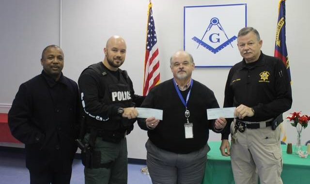 U.S. - Freemasons present checks for Shop with a Cop